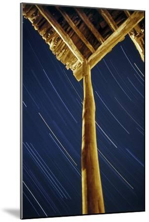 A Long Exposure of Sky Motion Shows Star Trails over the Wooden Roof of a Village House-Babak Tafreshi-Mounted Photographic Print