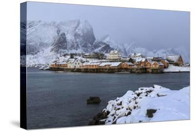 Snowy Peaks and Rorbu, the Red Houses of Fishermen, in the Landscape of the Lofoten Islands-Roberto Moiola-Stretched Canvas Print