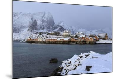 Snowy Peaks and Rorbu, the Red Houses of Fishermen, in the Landscape of the Lofoten Islands-Roberto Moiola-Mounted Photographic Print