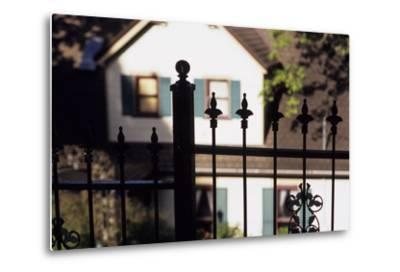 A Wrought Iron Black Fence Frames a Home with Blue Shuttered Windows-Paul Damien-Metal Print