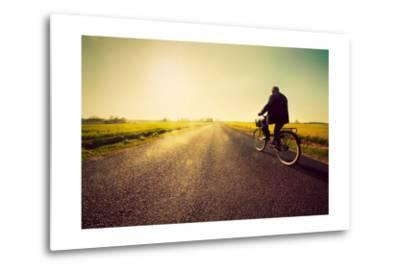 Old Man Riding A Bike On Asphalt Road Towards The Sunny Sunset Sky-Michal Bednarek-Metal Print