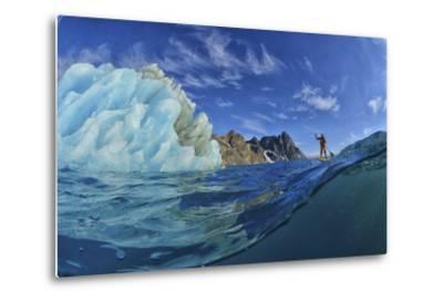 A Person Stand Up Paddle Boarding Near an Iceberg in the Fjords of Southeast Greenland-Keith Ladzinski-Metal Print