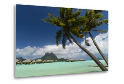 Over-The-Water Bungalows at a Tropical Resort with Clear Turquoise Water and Wind-Blown Palms-Sergio Pitamitz-Metal Print