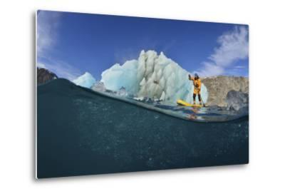 Stand Up Paddle Boarding by an Iceberg, in a Fjord in Southeast Greenland-Keith Ladzinski-Metal Print
