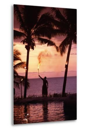 Native in a Grass Skirt Holding a Flaming Torch by Coast at Sunset-Design Pics Inc-Metal Print