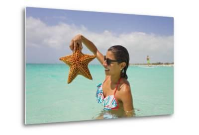 A Woman Holds Up a Starfish She Found in the Shallow Water Off of a Beach-Mike Theiss-Metal Print