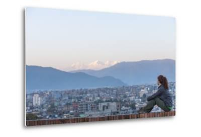 A Woman Sits on a Rooftop in Kathmandu and with the Ganesh Himal Mountain Range in the Distance-Alex Treadway-Metal Print