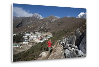 A Hiker Walks Past a Wall of Mani Stones Inscribed with an Ancient Tibetan Mantra-Alex Treadway-Metal Print