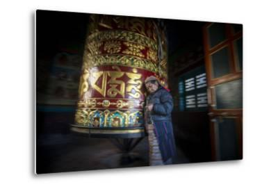 An Old Tibetan Woman Spins a Prayer Wheel While Counting Through a String of Rosary Beads-Alex Treadway-Metal Print