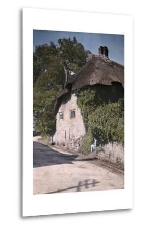 A Girl Sits on a Wall Next to an Old Thatched Cottage-Clifton R^ Adams-Metal Print