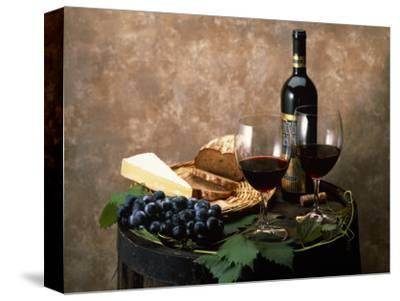 Still Life of Wine Bottle, Wine Glasses, Cheese and Purple Grapes on Top of Barrel--Stretched Canvas Print