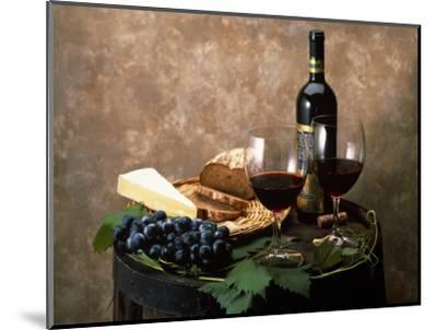 Still Life of Wine Bottle, Wine Glasses, Cheese and Purple Grapes on Top of Barrel--Mounted Photographic Print