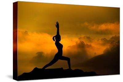 Silhouette of Woman Doing Yoga Meditation During Sunrise with Natural Golden Sunlight on Mountain-szefei-Stretched Canvas Print