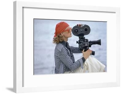 Side View of Model Holding a Movie Camera, Filming in Paradise Island, Bahamas-Gianni Penati-Framed Premium Giclee Print