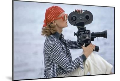 Side View of Model Holding a Movie Camera, Filming in Paradise Island, Bahamas-Gianni Penati-Mounted Premium Giclee Print