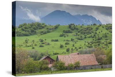 Romania, Transylvania, Bran, House and Bucegi Mountains, Spring-Walter Bibikow-Stretched Canvas Print