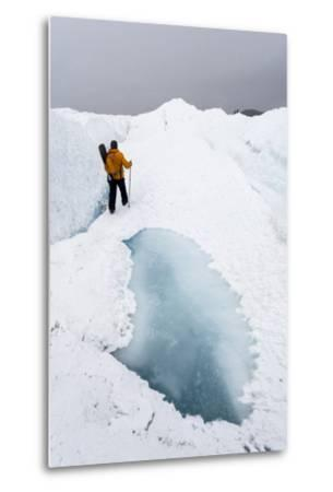 A Hiker Passing Between a Dangerous Crevasse and a Melt Pond on the Greenland Ice Shelf-Jason Edwards-Metal Print