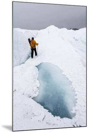 A Hiker Passing Between a Dangerous Crevasse and a Melt Pond on the Greenland Ice Shelf-Jason Edwards-Mounted Photographic Print