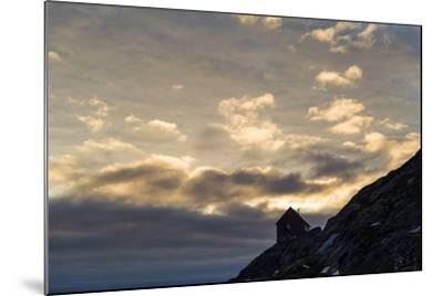 The Silhouette of a Cottage Perched on a Rocky Outcrop on an Arctic Island-Jason Edwards-Mounted Photographic Print
