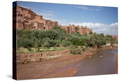 A Man on a Donkey Crossing the River in Front of Ait Benhaddou, Morocco-Erika Skogg-Stretched Canvas Print