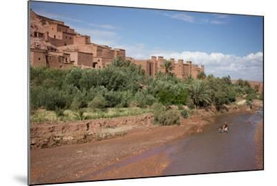 A Man on a Donkey Crossing the River in Front of Ait Benhaddou, Morocco-Erika Skogg-Mounted Photographic Print