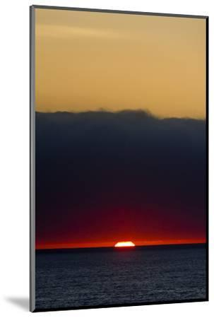 A Slither of Sunlight Pierces a Storm Cloud Above a Darkened Ocean at Sunset-Jason Edwards-Mounted Photographic Print