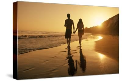 A Couple Walking on the Beach at Sunset-Macduff Everton-Stretched Canvas Print