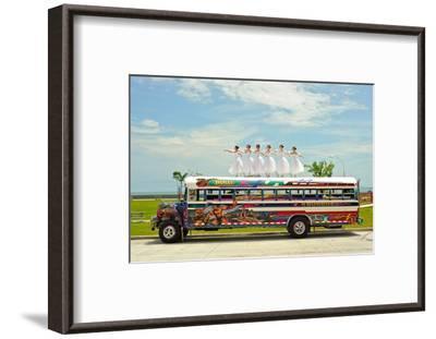 Ballerinas Dance on Top of a Diablo Rojo Bus on La Cinta Costera, Panama's Coastal Highway-Kike Calvo-Framed Premium Photographic Print