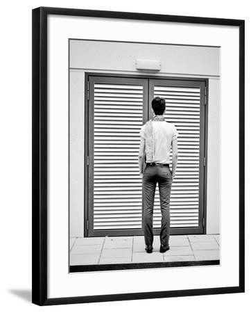 A Young Man Standing in the Street Looking at a Pair of Doors-India Hobson-Framed Photographic Print