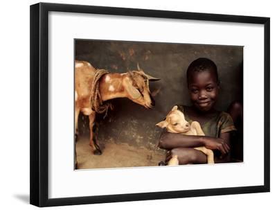 Child Holding a Kid-Mauro Fermariello-Framed Photographic Print