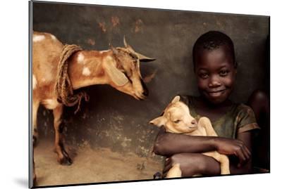 Child Holding a Kid-Mauro Fermariello-Mounted Photographic Print