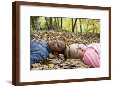 Smiling Children Lying on Autumn Leaves-Ian Boddy-Framed Photographic Print