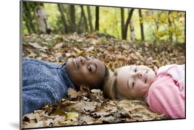 Smiling Children Lying on Autumn Leaves-Ian Boddy-Mounted Photographic Print