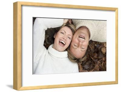 Laughing Couple Lying on Autumn Leaves-Ian Boddy-Framed Photographic Print