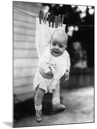 Baby (6-11 Months) Attached to Clothesline--Mounted Photographic Print