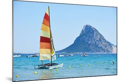 Scenic Italy Sardinia Beach Resort Landscape with Sail Boat and Mountains-kadmy-Mounted Photographic Print