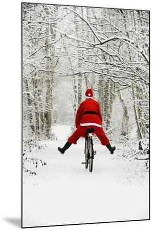 Father Christmas Riding Bicycle in Snowy Woodland Path--Mounted Photographic Print