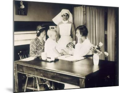 Doctor Examines a Baby at a Dispensary--Mounted Photographic Print