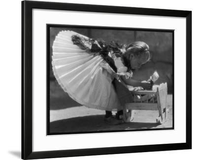 Young Romanian Girl Leans to Pick up Her Small Doll from a Beautifully Crafted Wooden Crib--Framed Photographic Print