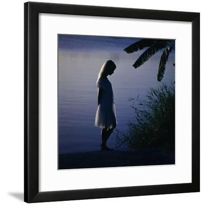 Silhouette of woman standing near a lake-Dennis Hallinan-Framed Photographic Print