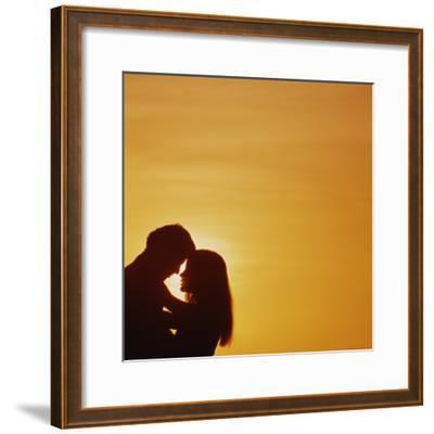 Silhouette of couple embracing at sunset-Dennis Hallinan-Framed Photographic Print