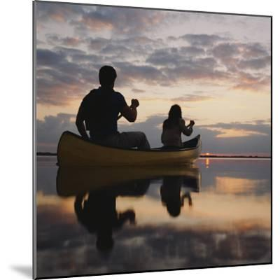 Couple Rowing Canoe in Lake at Sunset-Dennis Hallinan-Mounted Photographic Print