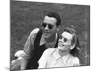 Couple Wearing Sunglasses Sitting on Grass, (B&W)-George Marks-Mounted Photographic Print