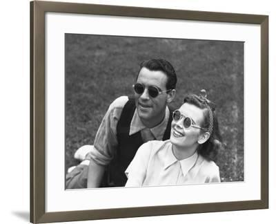 Couple Wearing Sunglasses Sitting on Grass, (B&W)-George Marks-Framed Photographic Print