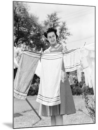 Woman Wearing a White Collar Poka Dot Cotton Dress While Pinning a Towel on a Clothes Line-H^ Armstrong Roberts-Mounted Photographic Print