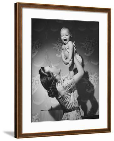 Woman Lifting Up Baby (6-9 Months) at Home-George Marks-Framed Photographic Print