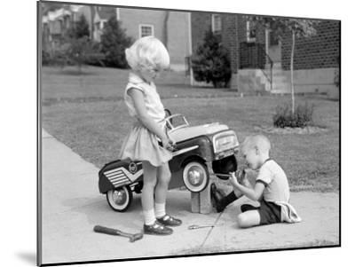 Children on Suburban Sidewalk, Boy Playing As Mechanic, Oiling Toy Pedal Car-H^ Armstrong Roberts-Mounted Photographic Print