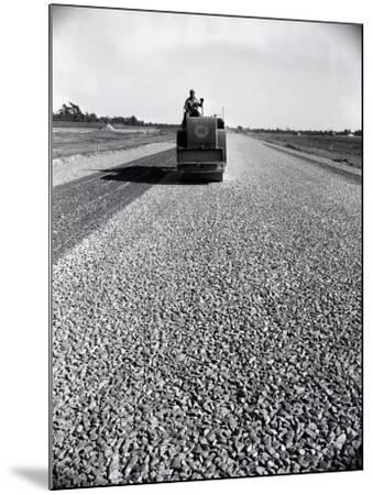 Highway Construction Worker Operating Heavy Machinery on Loose Gravel Road-H^ Armstrong Roberts-Mounted Photographic Print