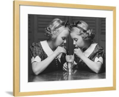 Twin Sisters Drinking Through Straws From Same Glass-George Marks-Framed Photographic Print