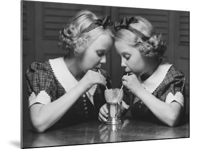 Twin Sisters Drinking Through Straws From Same Glass-George Marks-Mounted Photographic Print